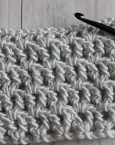 crochet white yarn dark crochet hook on white background