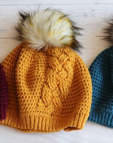 three crochet hats white background red yellow blue