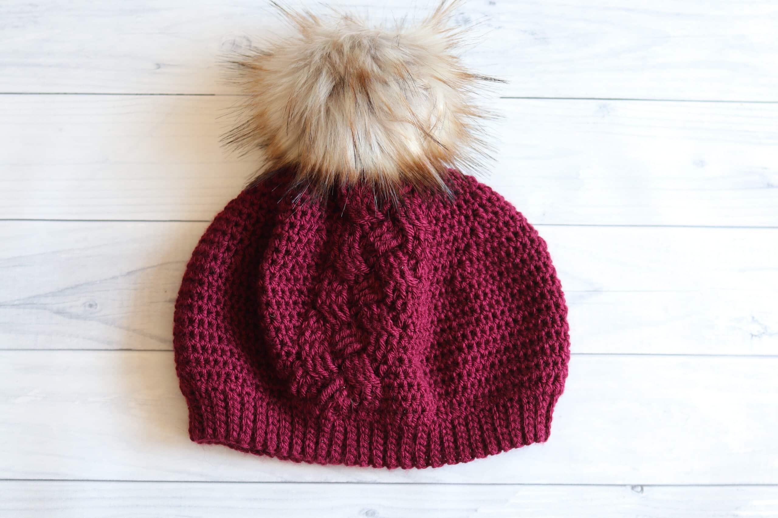 red crochet hat white pompom white background