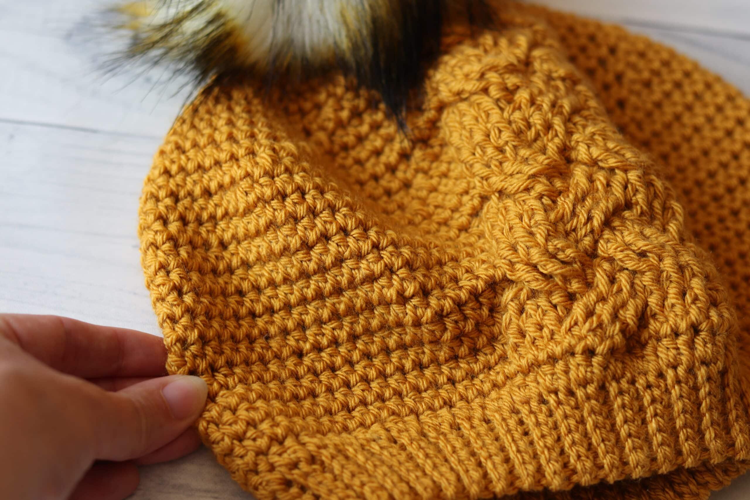 hand holding yellow crochet hat white background