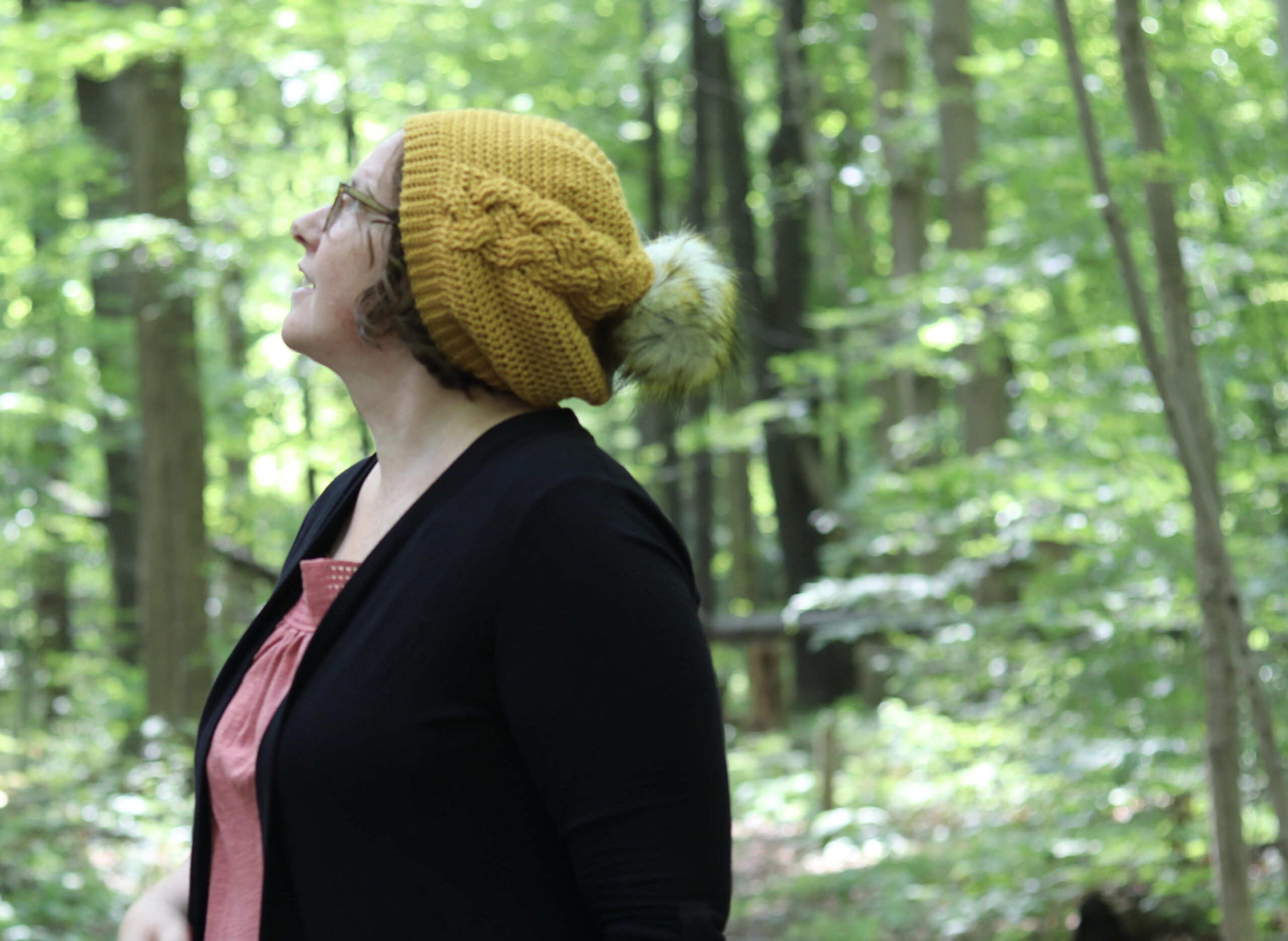 yellow hat white pompom worn by woman in forest