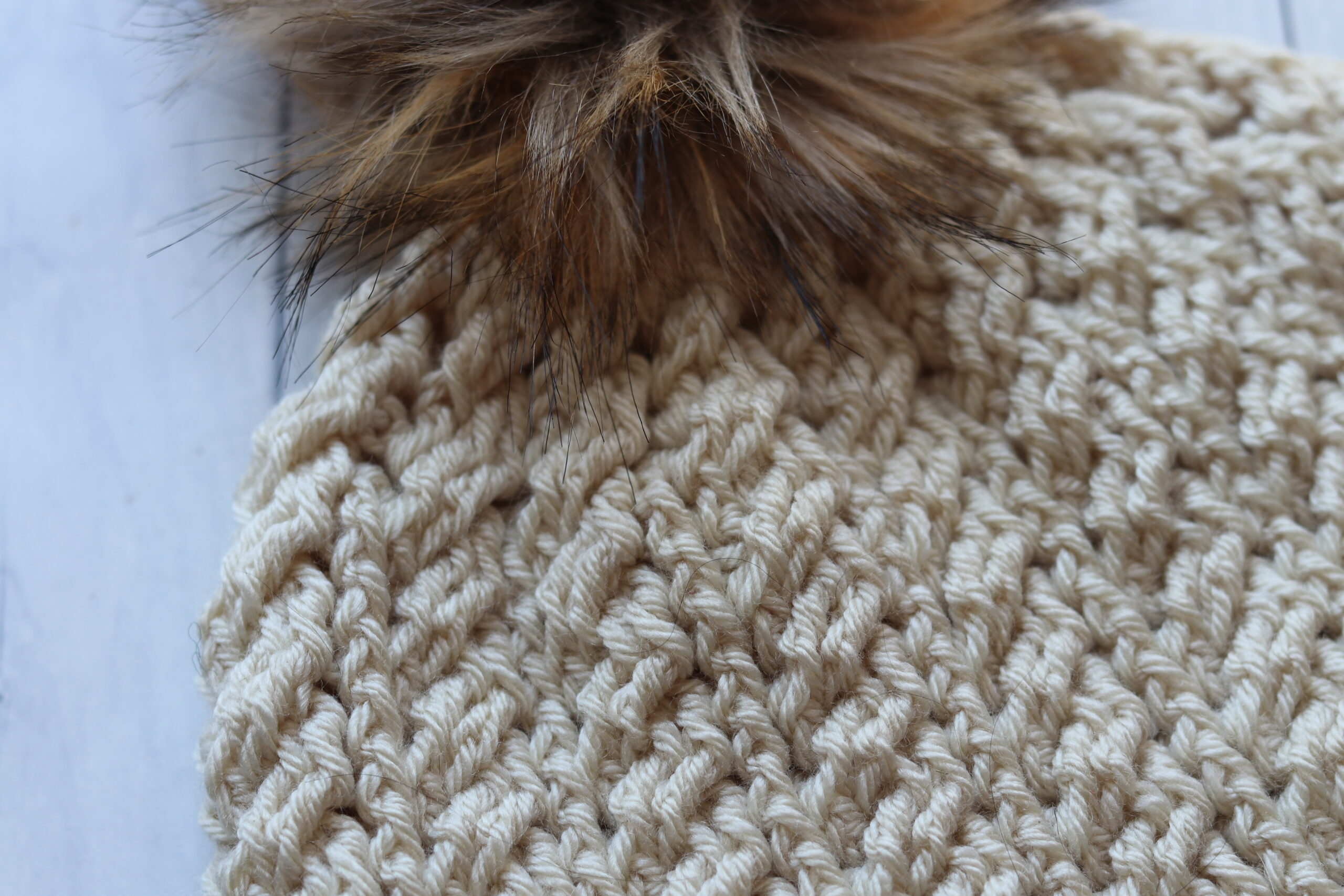 close up off white crochet hat with brown pompom on white background