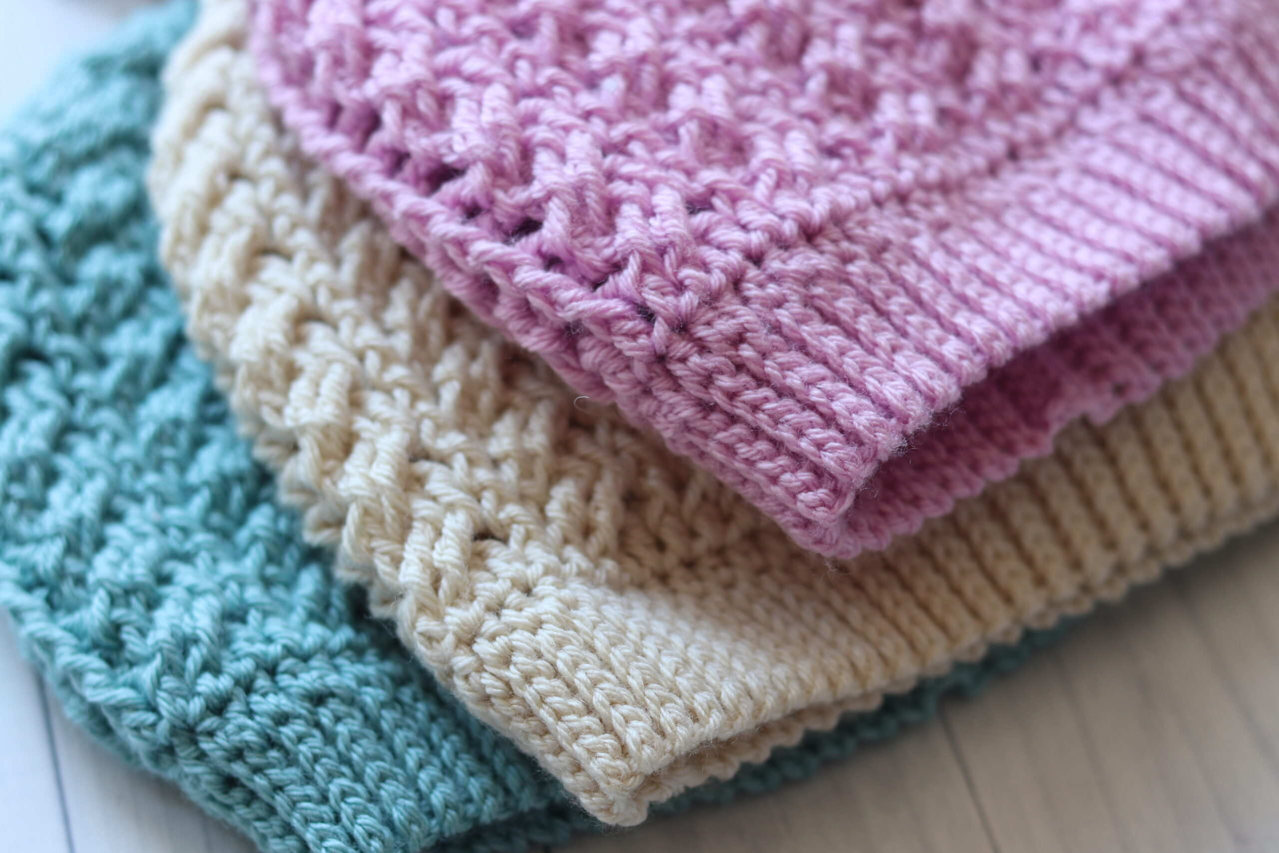 three crochet hats in blue white and pink close up