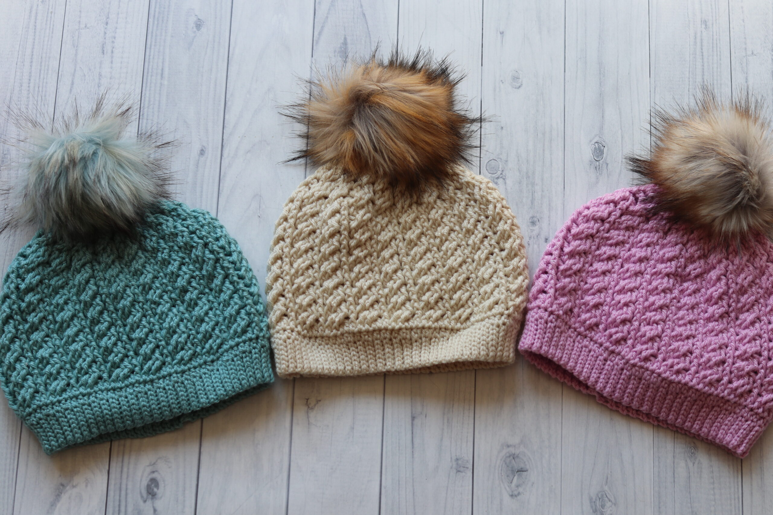 three textured hats with pompoms teal white pink with white background