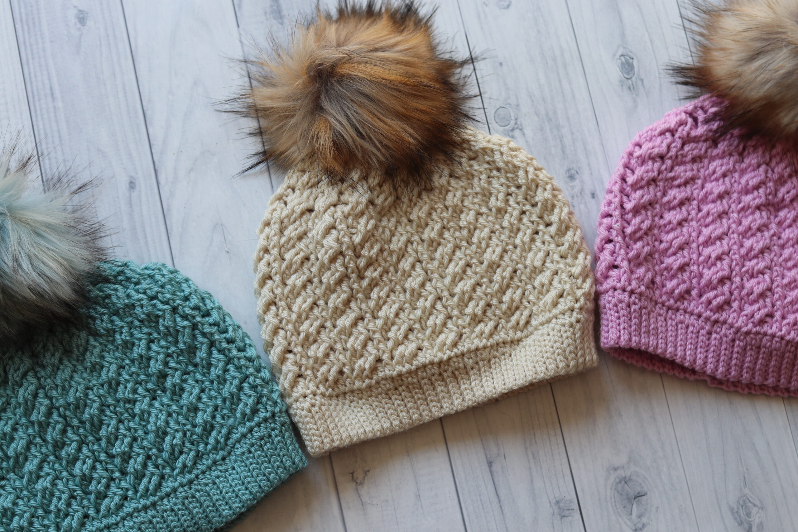 three crochet hats displayed on an angle in three different colours