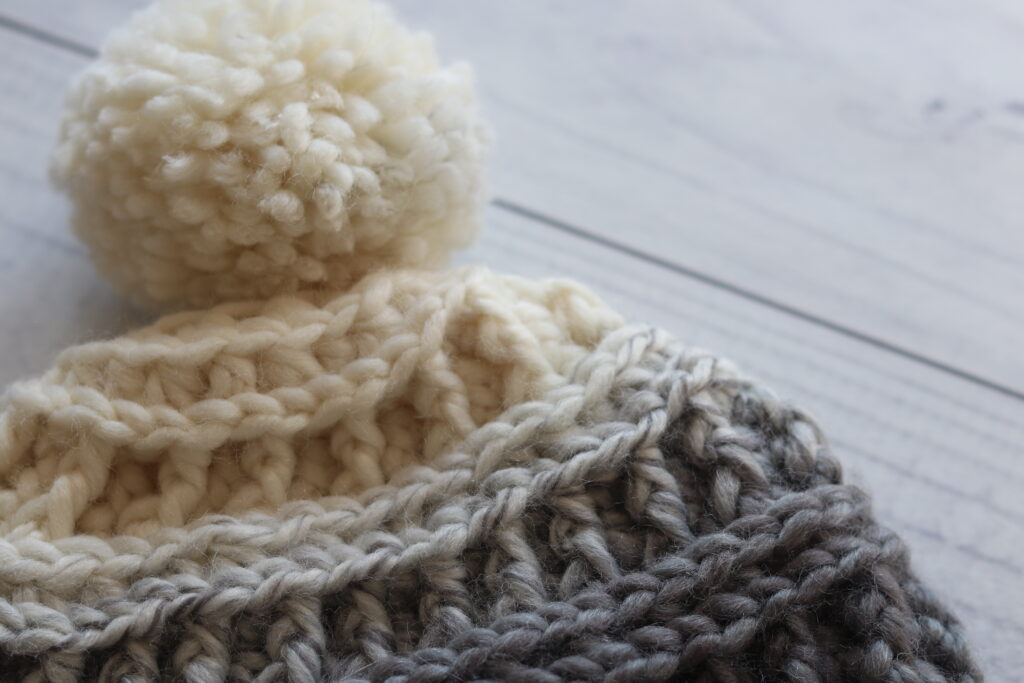 close up of crochet hat top with pompom