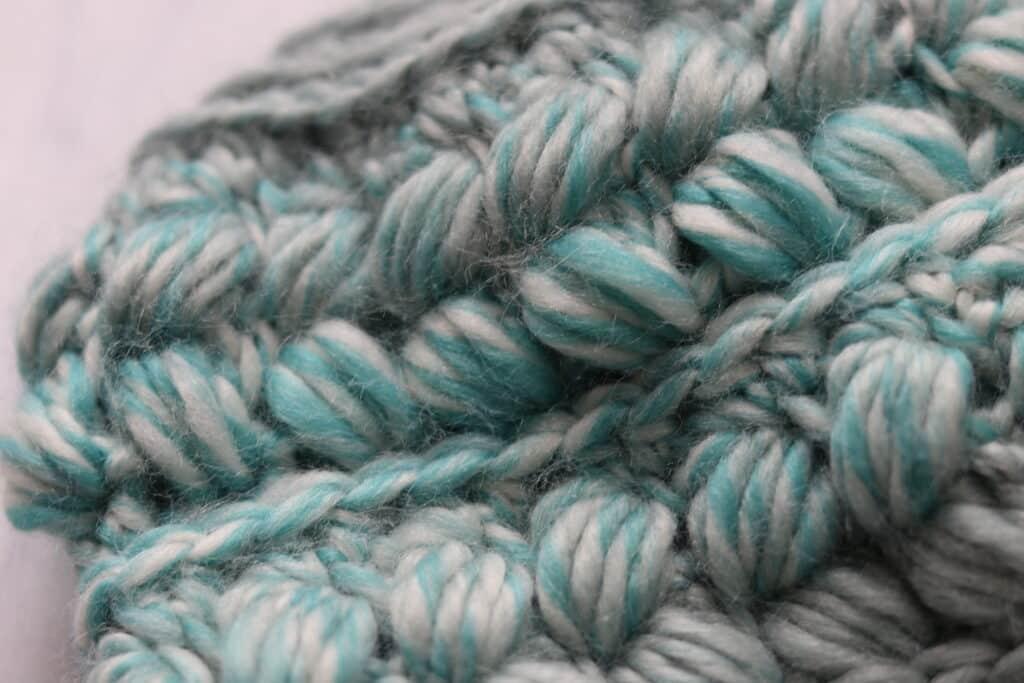 close up of braided puff stitch beanie in teal