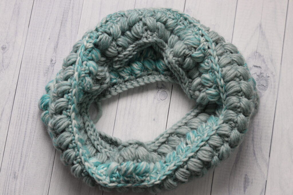crochet cowl displayed in a circle in the colour teal