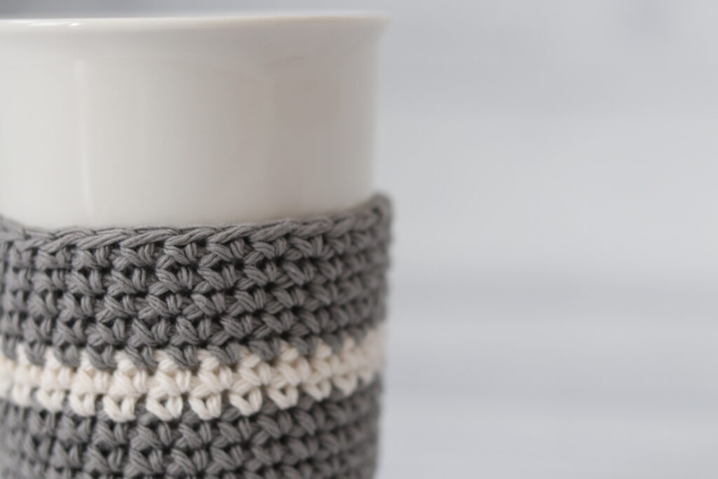 close up grey cup cozy with white stripe