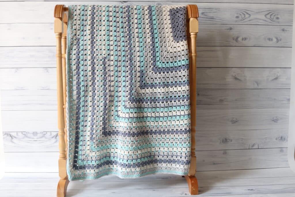 blue white and grey crochet blanket on quilt rack
