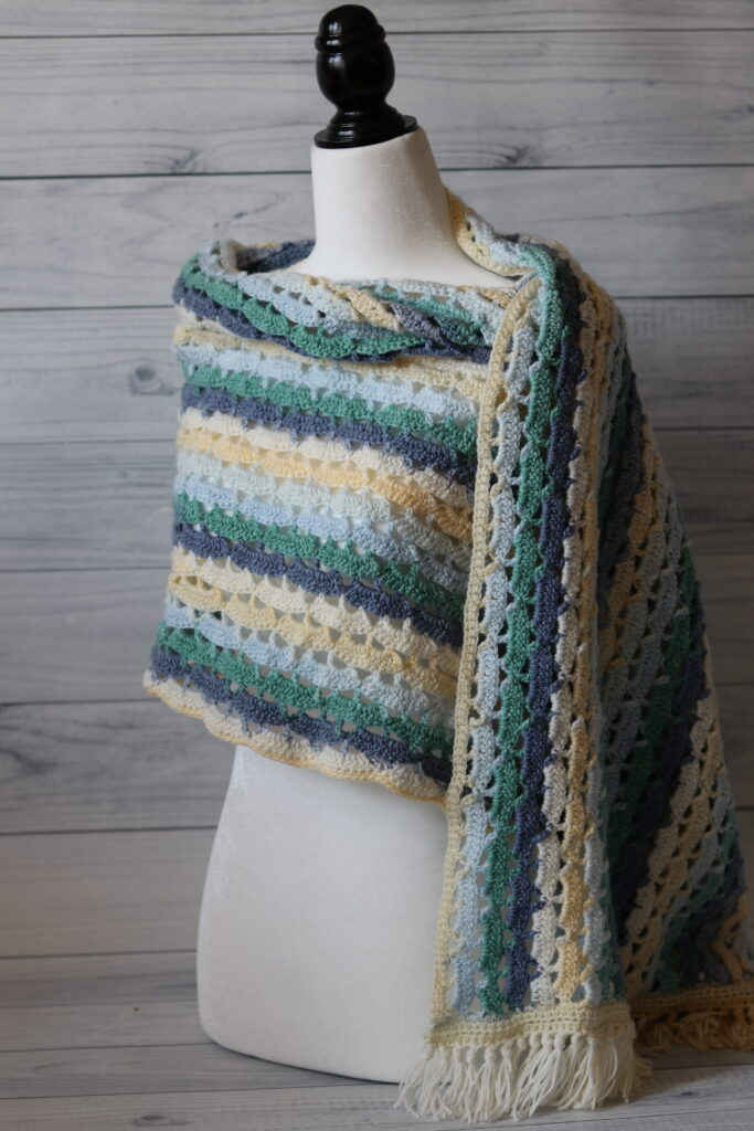 lacy crochet shawl in blue white and yellow