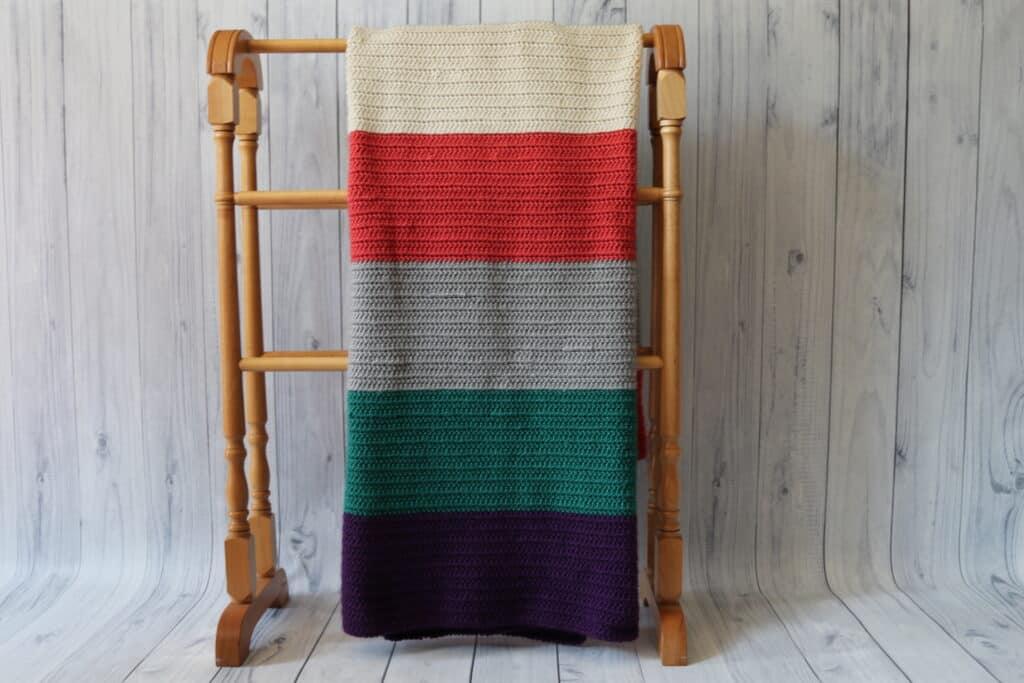 Crochet blanket hanging on quilt rack