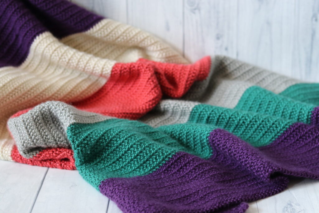 crochet blanket laid on floor in colours purple green grey white and pink