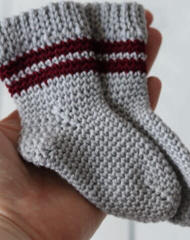 hand holding baby sized pair of crochet socks