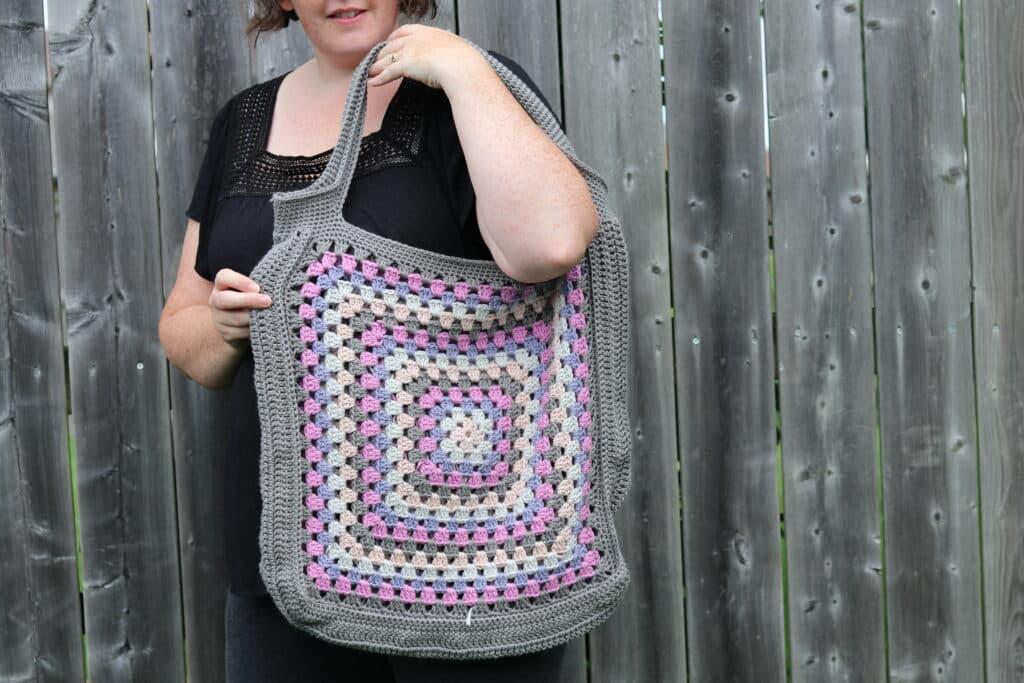woman holding granny square market bag
