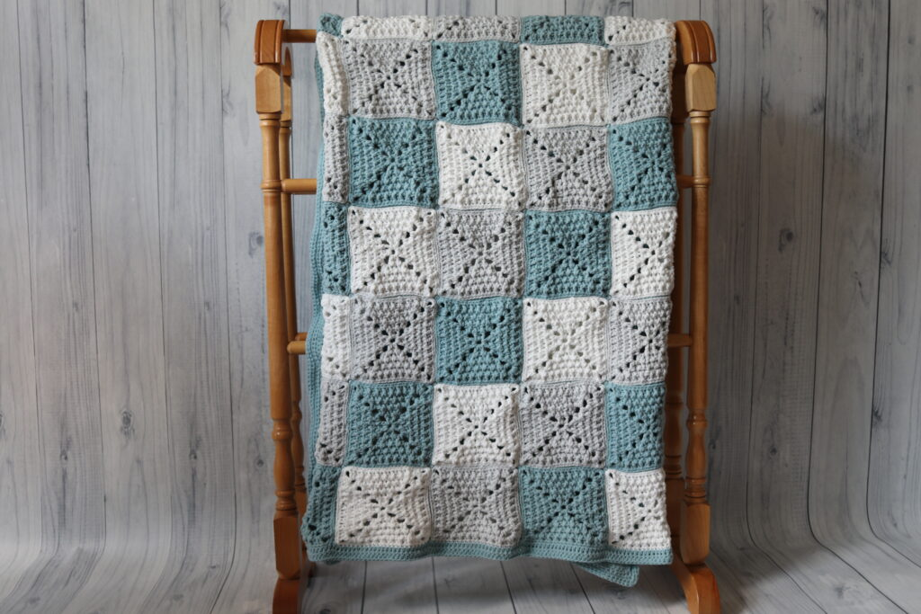 checkered blanket hanging on a quilt rack