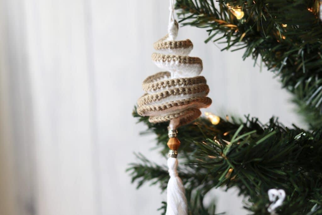 one crochet spinner ornament hanging on Christmas tree