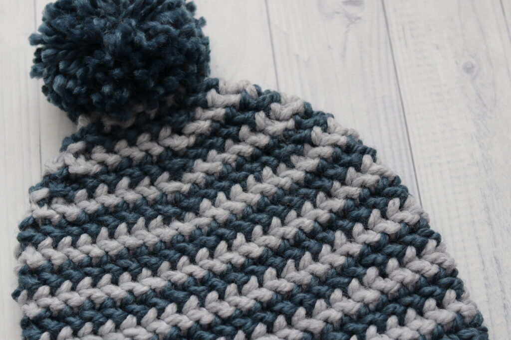 close up of a grey and blue crochet beanie