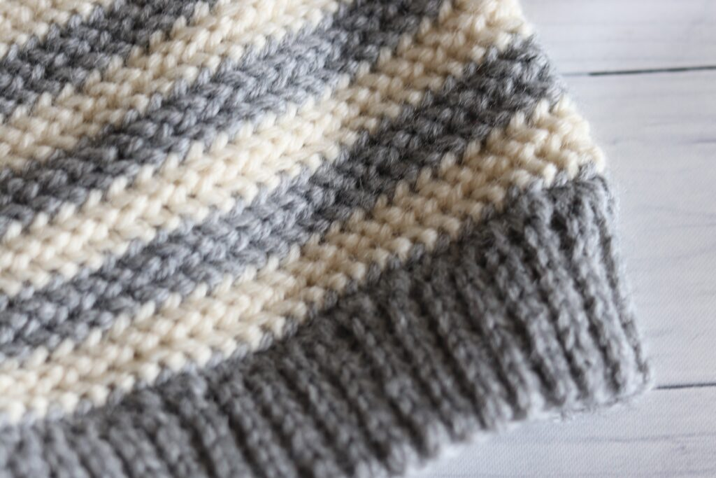 close up of brim on a grey and white crochet beanie